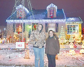 """Chuck Dressel and his fiancee, Jenn Rogers, of Youngstown pose outside their home on Hazelwood Avenue. Dressel has put on a show for six years and now has the lights timed to music. """"Our display focuses on everything,"""" Dressel said. """"I don't want to focus all on lights."""""""