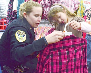"""Capt. Stacy Karis of the Lowellville Police Department helps Reese Agee, 5, of Poland pick out a shirt during the Shop with a Cop program at Walmart in Boardman on Sunday. About 90 children in need took part in the event, in which they were accompanied by police officers and firefighters, mostly from Struthers and Lowellville, to shop for clothes, toys and other items. """"It's all about giving back to the community,"""" Karis said."""
