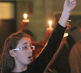 William D Lewis The Vindicator Grace rusko, 11, of Canfield holds a candle and sings Silent Night during Christmas Eve service at Western Reserve United Methodist Church in Canfield.