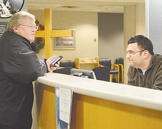 Jason Axelson, a volunteer with B'nai B'rith and Operation Snowflake, greets visitor Eric Ronan at St. Elizabeth Health Center in Youngstown. Members of the Jewish service organization and others volunteered at the information desk and the gift shop on Christmas Day to give Christian workers the day off .