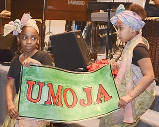 """Melea Lewis, left, and Amira Monserrat hold a sign reading """"Umoja,"""" which means unity, during a celebration for the first night of Kwanzaa at New Bethel Baptist Church on Thursday. Three other Youngstown churches also will host Kwanzaa celebrations in the next week."""
