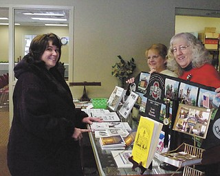 """SPECIAL TO THE VINDICATOR For new members, Salem Historical Society is offering the choice of the book """"The Salem Story Continues"""" or a table runner of the 150th anniversary of Salem Public Schools. The newest member, Lisa Brauner, left, chose the table runner. She is assisted by society gift shop volunteers Priscilla Wilde and Alice Deathrage. Brauner recently moved to Salem from Oklahoma. Membership information is available at the gift shop, 239 S. Lundy Ave., on Monday, Wednesday or Thursday mornings or by mail at Salem Historical Society, 208 S. Broadway Ave., Salem, OH 44460 or call 330-337-8514."""