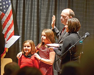 Flanked by his daughters, Cara and Casey, and wife, Virginia, John A. McNally takes the oath of office as Youngstown's 50th mayor Monday at DeYor Performing Arts Center downtown.