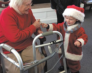 SPECIAL TO THE VINDICATOR: Paxton Gabbert, 3,  Santa's little helper, spread Christmas cheer recently to the residents of Whispering Pines Village in Columbiana. Above is resident Martha Bell, enjoying his company and pleased by his gift of a candy cane. Whispering Pines is an assisted-living and independent-living facility at 937 E. Park Ave.