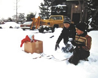 "From Kathy Miller: ""In either December 1984 or January 1985, our third son, Tyler, was 7 or 8 months old and wanted to be with the older kids outside. They created the box on the sled and pulled him around the yard. My mother-in-law had made the little red winter jacket for Tyler. Friend and neighbor up the street on Creston in Boardman (we still live there) is Stephen Bupp and Tyler's older brother, Nathan, in beige/tan jacket dreamed up the box on a sled idea. I sent this to my family in an email as a quiz on Christmas asking who were in the picture and what year it was taken. It was hard to believe that no one got it right. The years have sure flown by."""