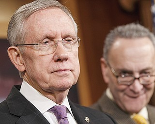 Senate Majority Leader Harry Reid of Nevada, left, accompanied by Sen. Charles Schumer, D-N.Y., listens during a news conference on Capitol Hill in Washington. Congress returns to work today with election-year politics certain to shape the agenda.