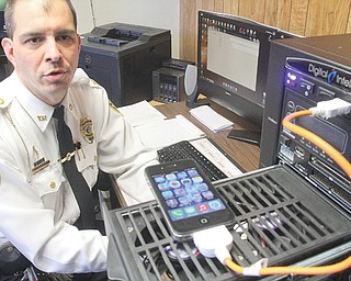 Youngstown police Capt. Jason Simon demonstrates the way a cellphone can be checked in the department's