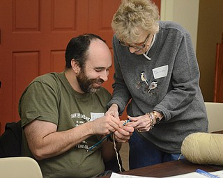 Dorothy Voitus teaches Joe Marino some of the fine points of knitting during a class recently at the Boardman branch of the Public Library of Youngstown and Mahoning County.