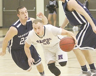 Mount Union's Nate Jacubec, a Struthers graduate, drives through Marietta defenders Brennan McKean (22) and Andy Stegman (33) during a game Wednesday at Mount Union in Alliance. The Purple Raiders edged the Pioneers, 73-72.