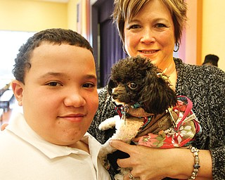 Rhyan Pegues, a fifth-grader at Youngstown's McGuffey Elementary School, and Paula Cipriano, a special-education teacher at the school who works with Legacy Dog Rescue, pose with Nessa, a dog Legacy found a new home for after Dr. John Owen, a Howland veterinarian, repaired her broken leg.