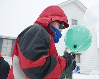 Nicolas Stafford holds onto balloons outside the home in Struthers where Teddy Foltz, 14, was living when he