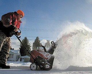 Norm Capp of Youngstown, bundled up as he braves the conditions Monday, uses a snowblower to clear a friend's driveway on Chaney Circle in Youngstown. Today's high temperature is expected to be 2 degrees with wind chills as low as 28 below zero.