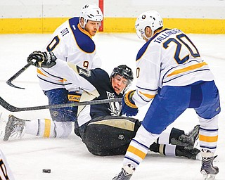 Penguins captain Sidney Crosby (87) reaches for the puck after colliding with Sabres defender Steve Ott (9) behind teammate Henrik Tallinder (20) in Monday's game in Pittsburgh. The Pens won, 3-0.