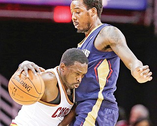 The Cavaliers' Luol Deng, left, drives around the Pelicans' Al-Farouq Aminu during the first quarter of their