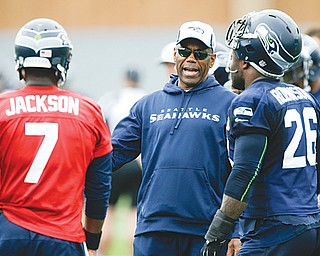 Seattle running backs coach Sherman Smith, center, talks with Seahawks backup quarterback Tarvaris Jackson (7) and fullback Michael Robinson (26). Before he was a coach with his second Super Bowl team … before he spent eight years as an NFL player … before he won three Mid-American Conference titles as Miami's (Ohio) first black quarterback, Smith was a Youngstown teen who couldn't see past the city limits.
