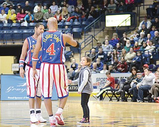 "The Harlem Globetrotters ""Handles"" and ""Flight Time"" invite Maria Goske, 6, out onto the court to teach her a few basketball tricks during Wednesday's performance at the Covelli Centre."