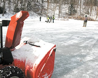 Mill Creek MetroParks employees clear the snow off the Lily Pond on Thursday. Some areas of the ice are about