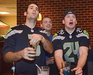Seahawk fans (L-R) Philip Cogar, Jacob Short, and Will Ferrand react to a play during the first quarter of the Super Bowl.  They are among a small crowd gathered at Inner Circle Pizza in Canfield to watch the game.