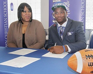 Kambria Brown, watches as her son, Youngstown Christian defensive lineman Tymere Dubose, signs his