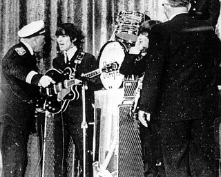 Police Inspector Carl Bear of Cleveland's Juvenile Bureau, left, orders George Harrison and the other members of the British pop group The Beatles, off the stage of the Public hall, Cleveland, Ohio, Sept. 16, 1964 as teenagers rushed the stage. Bear let the group back on ater wailing youngsters were given 15 minutes to cool down. From left to right, Bear, Harrison, John Lennon, unknown, and Ringo Starr, top right. (AP Photo)