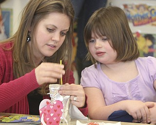 William D.Lewis The Vindicator Austintown Elem school kindergarten teacher Jen Kalouris helps student Emily with a Valentines craft project a Valentines day party at the school 2-13.