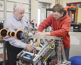 Girard's Lane Tuttle, 17, measures PVC pipe on the test robot with the help of robotics mentor Mark Walker Monday, February 17, 2014.