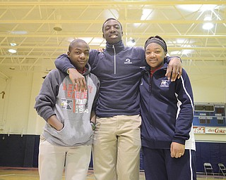 Warren JFK basketball player James Burney Jr., center, poses with his 13-year-old brother Quintin Burney, left, and sister Taejah Burney, 15, in the gymnasium at Warren JFK High School on Tuesday. Basketball has become an outlet for grief for the siblings after the unexpected death of their mother Timika Burney, last month.