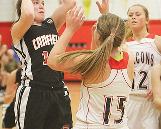 Canfield's Lynnae Whitehead looks to shoot over Fitch's Cassier Custer (15) and Sarah Melfe (12) in a Division I sectional final Thursday at Fitch High School in Austintown. The Cardinals downed the Falcons, 53-45.