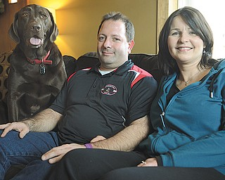 Missy Ginnetti, right, poses with husband Patrick Ginnetti and dog Max in their Struthers home. Missy has been fighting Hodgkin lymphoma on and off since being diagnosed in June 2010, and soon may undergo an allogeneic stem-cell transplant.