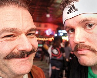 Youngstown Police officers Mike Marciano, left, and Michael Fox, sport mustaches during a party Wednesday at Royal Oaks in Youngstown. City officers on midnight turn organized a mustache contest as a fundraiser for the Michael Hartzell scholarship fund. Hartzell was a police officer killed in the line of duty in April 2003.
