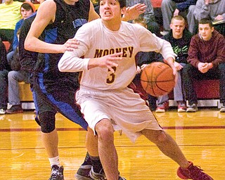 Mooney forward Ross Lanzo drives toward the basket against Lakeview defender Tom Bell during the first half of their Division II sectional semifinal Wednesday at Cardinal Mooney High School in Youngstown. The Cardinals downed the Bulldogs, 53-30.