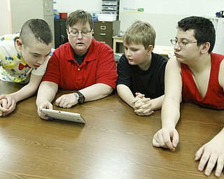 ROBERT K. YOSAY  | THE VINDICATOR..Sister Martha works with an I Pad on quick math problems. l-r  Tyler Wolfrod -Becky- Cory Fielder -  Halston Glaspell.Sister Becky Reed at Potential Developement center ...... - -30-.       ROBERT K. YOSAY  | THE VINDICATOR......... - -30-.