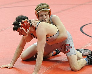 COLUMBUS, OHIO - FEBRUARY 28, 2014: Korey Frost of Canfield holds on to the leg of Dustin Warner of Uhrichville Claymont as the two wrestle on the mat during their 120lb championship bracket bout during the 2014 division 2 state wrestling tournament at Schottenstein Center.