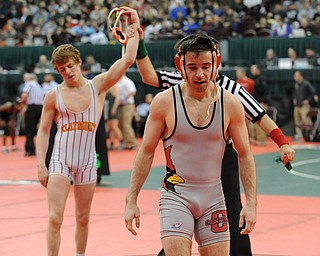 COLUMBUS, OHIO - FEBRUARY 28, 2014: Korey Frost of Canfield walks off the mat while Dustin Warner of Uhrichsville Claymont has his arm raised in victory by the referee after their 120lb championship bracket bout during the 2014 division 2 state wrestling tournament at Schottenstein Center.
