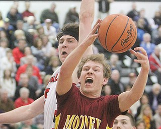 Cardinal Mooney's Joey Kleeh shoots past Canfield's Jarret Vrabel during their Division II district semifinal Thursday at Warren G. Harding High School. Mooney held off Canfield, 60-50, to advance to Saturday's final.