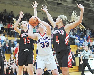 Western Reserve's Aleah Hughes is hemmed in by Bishop Rosecrans defenders Kloie Johnson (4) and Molly Nash (15) during the first half of their Division IV regional semifinal Thursday at Massillon Perry High School. The Blue Devils' season came to an end in a 67-31 loss to the Bishops.