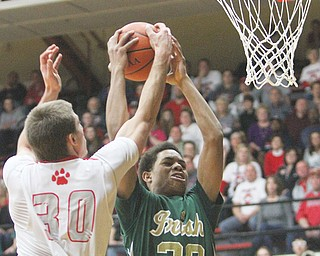 Ursuline's Dave Collins goes to the hoop past Trent Davis of Norwayne during the first half of their Division III regional semifinal Thursday at the Canton Fieldhouse. The Irish dominated the Bobcats, 74-56.