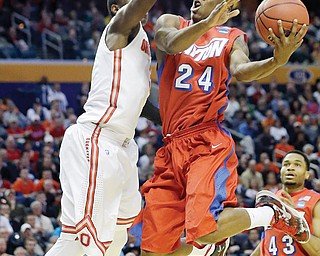 Dayton's Jordan Sibert (24) drives past Ohio State's Shannon Scott during the second half of a second-round