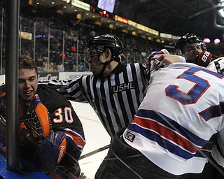 YOUNGSTOWN, OHIO - MARCH 21, 2014: Goalie Sean Romeo #30 is separated from Dennis Yan #57 of Team USA during a brawl during the 1st period of Friday morning against Team USA at the Covelli Centre. The Phantoms won 7-3.