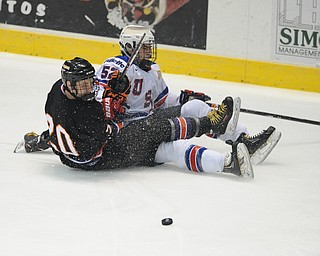 YOUNGSTOWN, OHIO - MARCH 21, 2014: Carson Gicewicz #20 of the Phantoms and Brody Stevens #52 of Team USA slide on the ground after colliding while trying to play the puck during the 2nd period of Friday morning against Team USA at the Covelli Centre. The Phantoms won 7-3.