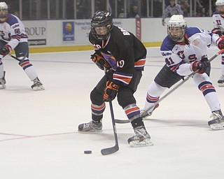 Trey Bradley (10) of the Youngstown Phantoms skates the puck down the ice while being defended by Team USA's Charles McAvoy (41) during the first period of Friday morning's matchupat the Covelli Centre.  Dustin Livesay  |  The Vindicator  3/21/14  Covelli Centre