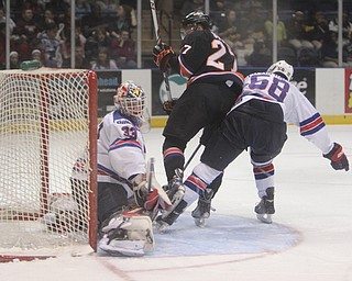 Luke Stork (27) of the Youngstown Phantoms flips in a goal past Team USA goalie Luke Opilka (33) and moved past the defense by Casey Fitzgerald (58) during the first period of Friday morning's matchupat the Covelli Centre.  Dustin Livesay  |  The Vindicator  3/21/14  Covelli Centre