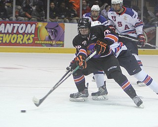 Connor Moore (28) of the Youngstown Phantoms skates the puck toward the goal while being defended by Team USA's Charles McAvoy (41) during the first period of Friday morning's matchupat the Covelli Centre.  Dustin Livesay  |  The Vindicator  3/21/14  Covelli Centre