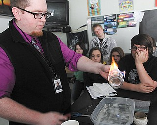 Scott Stoddart, a seventh-grade science teacher at Struthers Middle School, performs an experiment meant to illustrate why elements behave the way they do. Beginning this fall, Struthers schools will incorporate science, technology, engineering and mathematics into all levels of education.