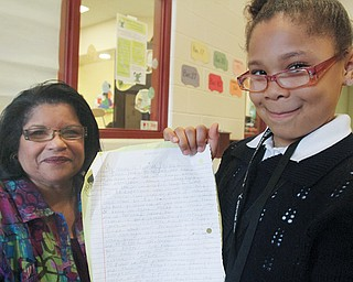 "Taniya Phillips, right, holds her first-place essay with Delphine Baldwin-Casey, commander of the Youth Police Academy. Taniya, a third-grader at Martin Luther King Elementary School, wrote the essay, ""Why I Never Want to Go to Jail,"" after a visit by the Youngstown City Schools Afterschool Alliance and the Youth Police Academy last month to the Martin P. Joyce Juvenile Justice Center in Youngstown."
