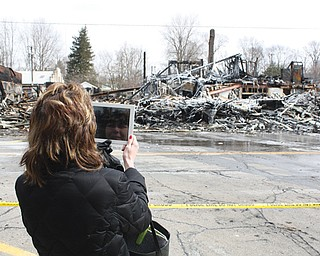 "Michelle Doherty of Newton Falls, who grew up in Garrettsville, takes a video of the remnants of four large buildings and 13 businesses on Main Street destroyed by a fire Saturday afternoon. Doherty said she remembered there being a ""five-and-dime"" store in the Buckeye Block building at the corner to the right. The Buckeye Block building was built about 1868. Future presidents William McKinley and James A. Garfield both spoke during meetings in Buckeye Hall on the building's upper floors."
