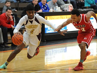 HOWLAND, OHIO - MARCH 25, 2014: Asim Pleas #4 of Liberty dribbles to the basket inside of Quincy Higgins #22 of Fitch during Tuesday nights Frank Bubba Classic boys basketball all-star game at Howland High School.