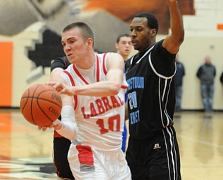 HOWLAND, OHIO - MARCH 25, 2014: Peyton Aldridge #10 of Labrae looks to pass the ball after dribbling into the paint and Terrell McClain of East was guarding during Tuesday nights Frank Bubba Classic boys basketball all-star game at Howland High School.