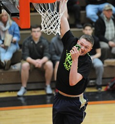 HOWLAND, OHIO - MARCH 25, 2014: Seth Wallace of Brookfield takes a selfie on his cell phone while slam dunking the basketball before of Tuesday nights Frank Bubba Classic boys basketball all-star game at Howland High School.