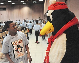 Harding Elementary School student Martize Daniels hangs out Thursday with Pete the Penguin during the Penguin Pen Pals get-together at Youngstown State University. Students from YSU and Harding wrote to each other throughout the school year and met Thursday.